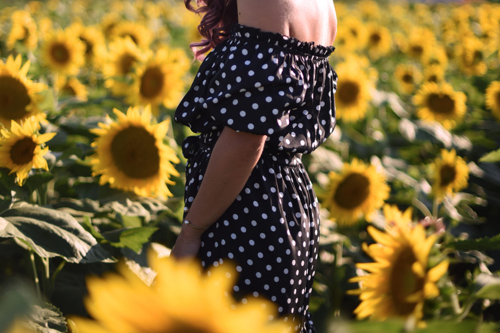 Un vestito nero lungo a pois in un campo di girasoli